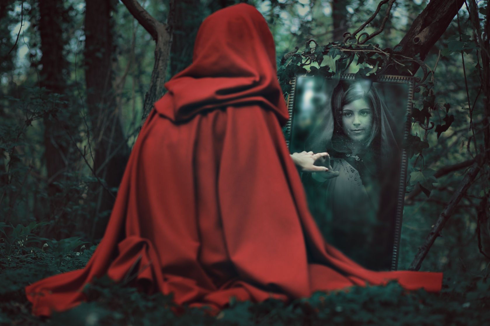 44701697 - mysterious red hooded woman in front of a magical mirror. dark fantasy
